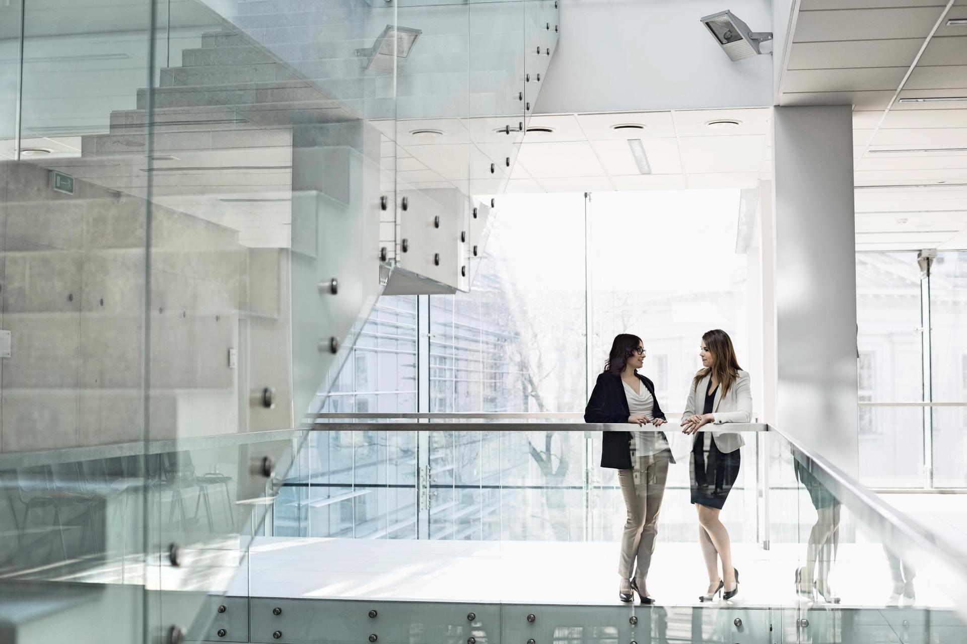 2 Frauen auf einer Treppe mit Glasgeländer